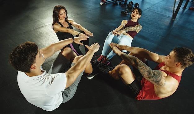 Um grupo de atletas musculosos fazendo exercícios na academia ginástica, treinamento de fitness