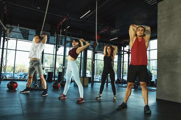Um grupo de atletas musculosos fazendo exercícios na academia ginástica, treinamento, fitness, treino
