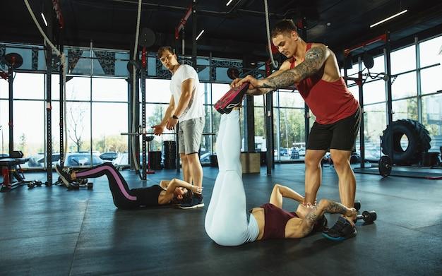 Um grupo de atletas musculosos fazendo exercícios na academia