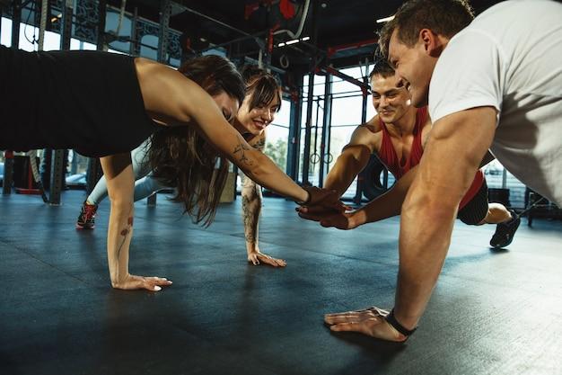 Um grupo de atletas musculosos fazendo exercícios no ginásio. ginástica, treino, flexibilidade de treino de fitness. estilo de vida ativo e saudável, juventude, musculação. treinamento em alongamento e prancha.