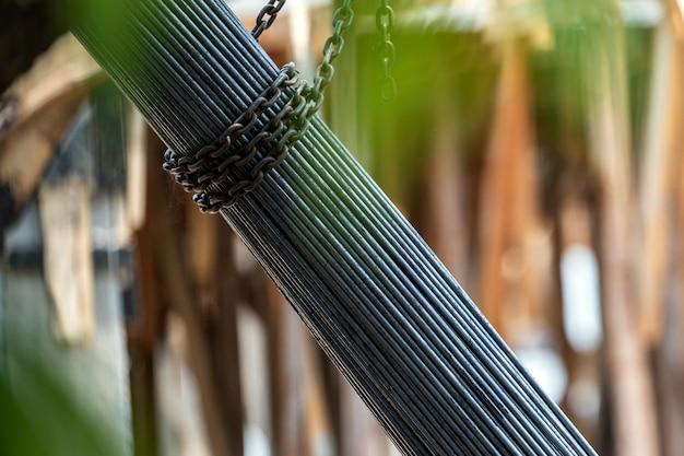 Um grupo de barra de aço apertado por corrente e levantando