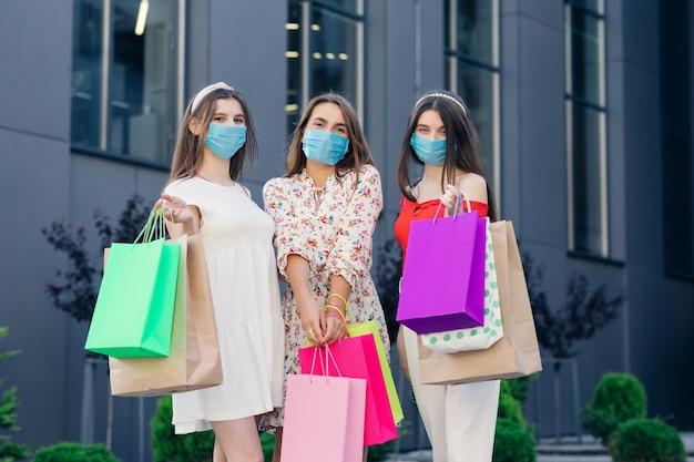 Um grupo de belas mulheres jovens em vestidos casuais, top e calças usando máscaras para proteger a pandemia do coronavírus em pé em frente ao shopping com sacolas coloridas nas mãos.