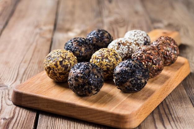Um grupo de bolas de energia deitado no papel pergaminho em uma placa de cozinha. mesa de madeira turva. o conceito de alimentação saudável.