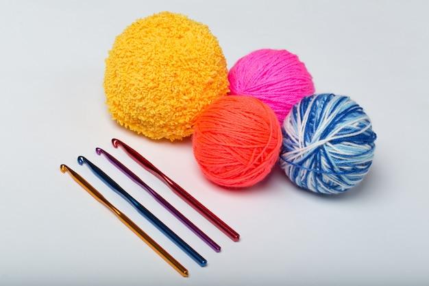 Um grupo de bolas multicoloridas de fios e agulhas de tricô em um fundo branco