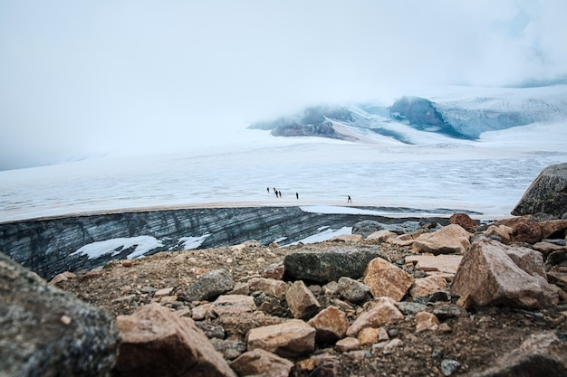 Um grupo de caminhantes escalando uma montanha nevando em uma manhã ensolarada de inverno