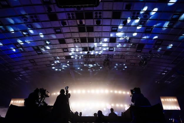 Um grupo de cinegrafistas trabalhando durante o show. evento de transmissão de televisão. silhuetas de trabalhadores contra vigas coloridas.