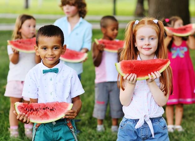 Um grupo de crianças alegres e felizes comem uma melancia madura no parque, na grama em um dia ensolarado de verão