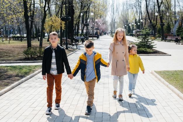 Um grupo de crianças brinca e caminha no parque de mãos dadas. amigos, filhos.