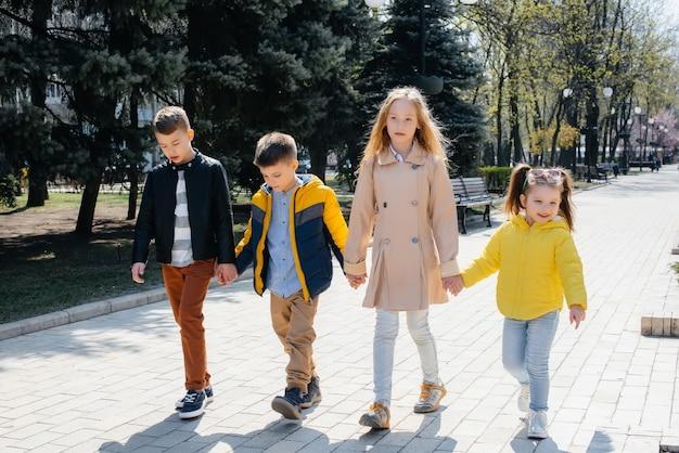 Um grupo de crianças brinca junto e caminha pelo parque de mãos dadas. amigos, filhos.