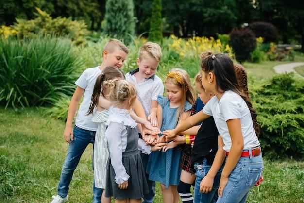 Um grupo de crianças corre, diverte-se e joga em equipa maior no verão no parque. infância feliz.