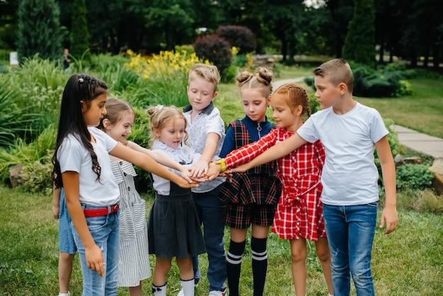 Um grupo de crianças corre, se diverte e joga como um time maior no verão no parque