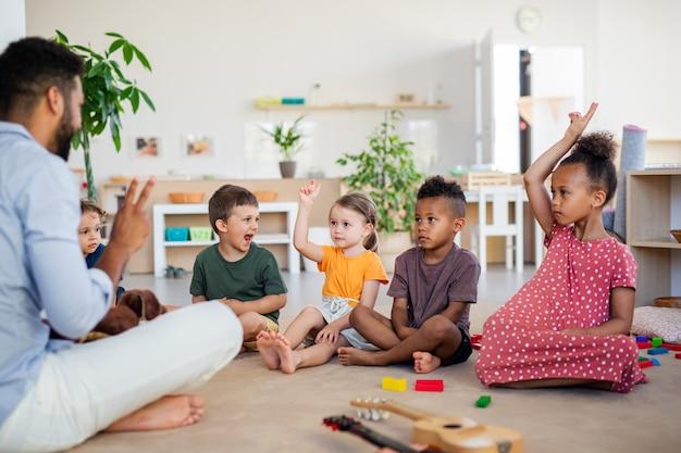 Um grupo de crianças da escola maternal pequenas sentadas no chão dentro de casa na sala de aula.