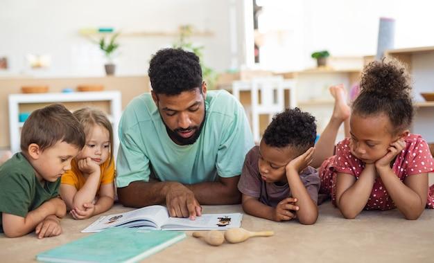 Um grupo de crianças de uma creche com um professor homem no chão dentro de uma sala de aula lendo um livro
