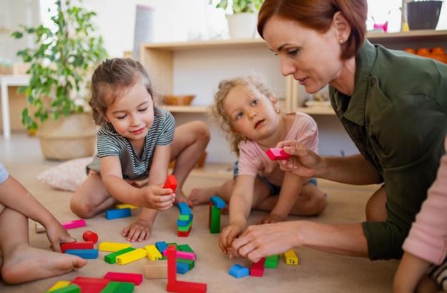 Um grupo de crianças de uma escola maternal pequena com o professor no chão dentro de casa na sala de aula, brincando.