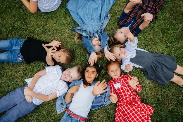 Um grupo de crianças em idade escolar deita-se na grama em círculo e se diverte. infância feliz.