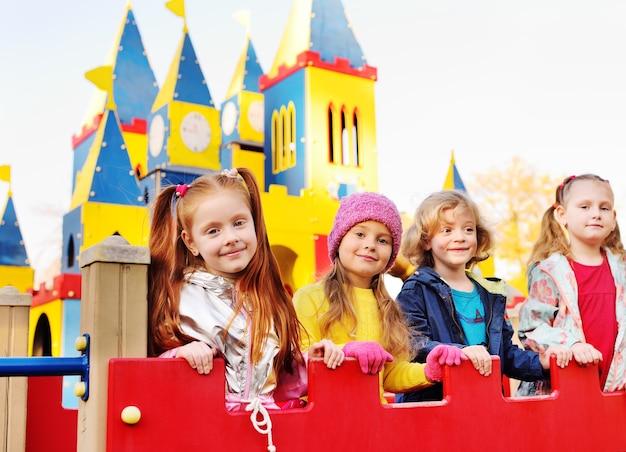 Um grupo de crianças em idade pré-escolar brinca e sorri no fundo de um parque de diversões infantil na forma de um castelo de conto de fadas