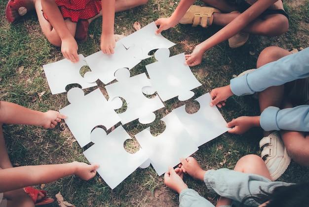 Um grupo de crianças etnicamente diversas se junta a peças de quebra-cabeças / quebra-cabeças no parquinho. conceito de trabalho em equipe, cooperação, aprendizagem e educação.