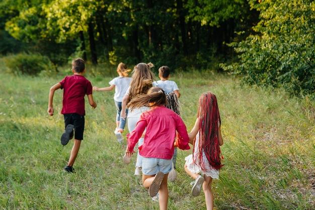 Um grupo de crianças felizes corre e brinca no parque durante o pôr do sol. acampamento infantil de verão.