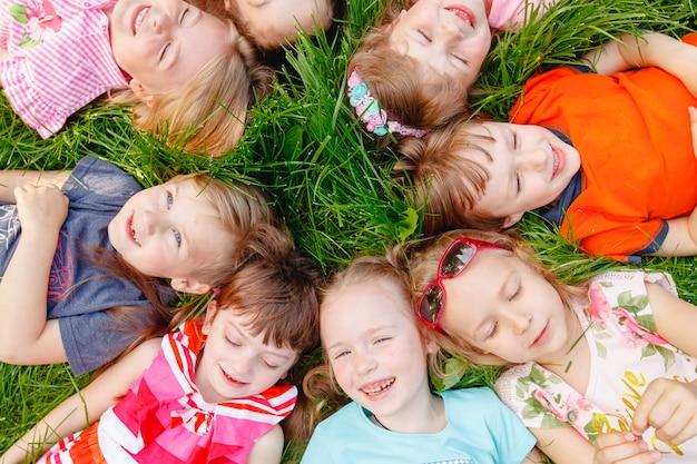 Um grupo de crianças felizes de meninos e meninas corre no parque na grama em um dia ensolarado de verão.