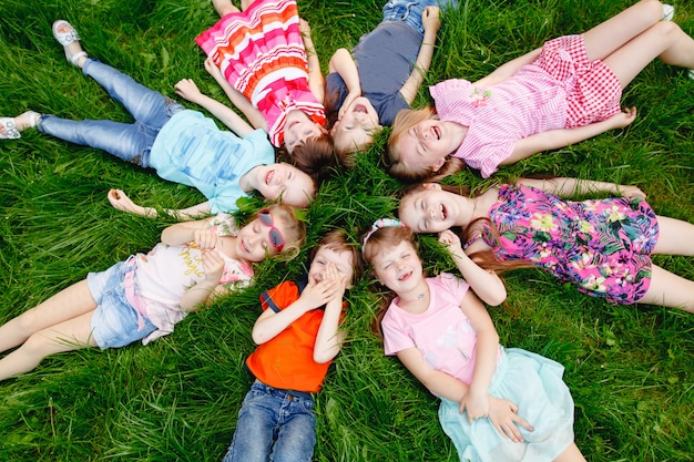 Um grupo de crianças felizes dos meninos e das meninas corre no parque na grama em um dia de verão ensolarado. o conceito de amizade étnica, paz, bondade, infância