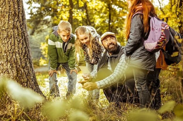 Um grupo de crianças olhando um cogumelo na mão de uma professora em um dia bom