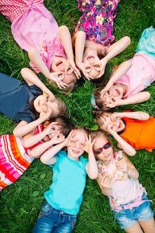 Um grupo de crianças que encontram-se na grama verde no parque.