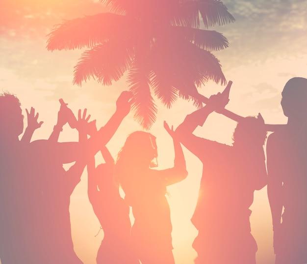 Um grupo de diversas pessoas dançando na praia