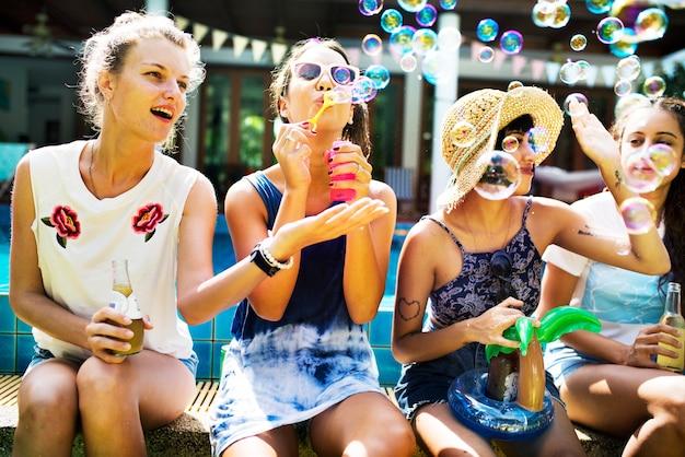 Um, grupo, de, diverso, mulher, amigos, sentar à beira piscina, tocando, com, um, soprador sabão