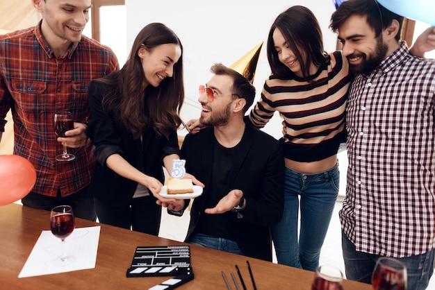 Um grupo de empregados de escritório celebra a empresa do dia.