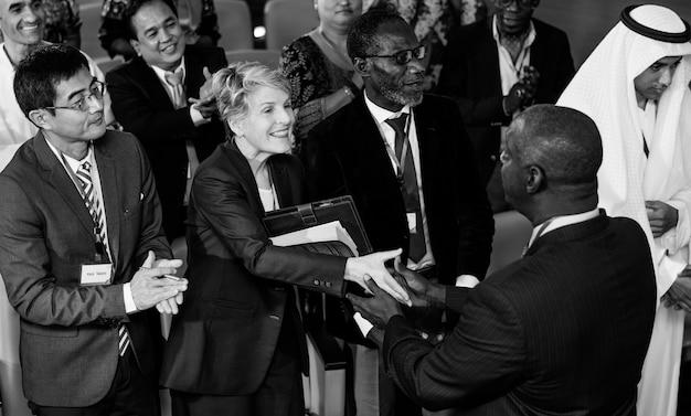 Um grupo de empresários internacionais cumprimenta uns aos outros