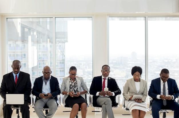 Um grupo de empresários internacionais está de pé e usando dispositivos sem fio