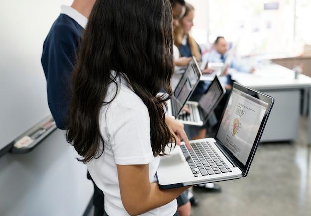 Um grupo de estudantes dando uma apresentação com laptops