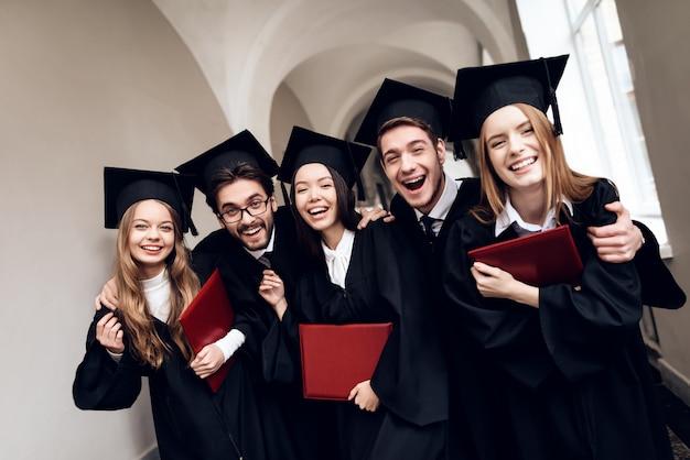 Um grupo de estudantes em mantos está de pé no corredor.