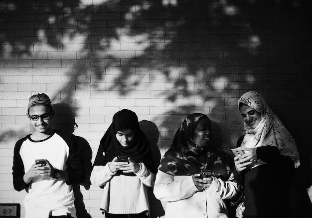 Um grupo de estudantes muçulmanos usando telefones celulares