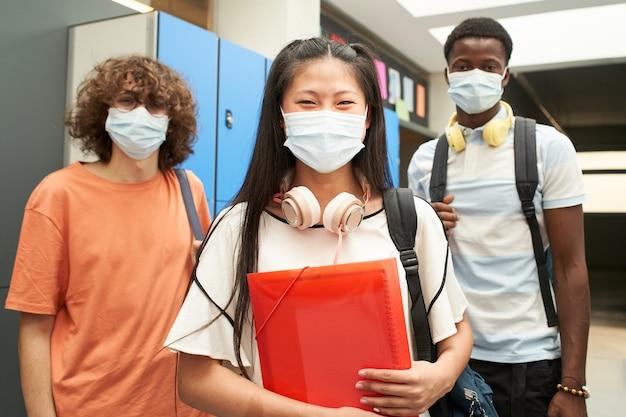 Um grupo de estudantes multirraciais com máscara olhando para a câmera sorrindo para a escola mascarada para prevenir e ...