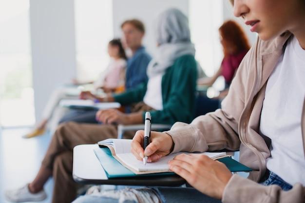 Um grupo de estudantes universitários irreconhecíveis sentados em uma sala de aula dentro de casa, estudando.
