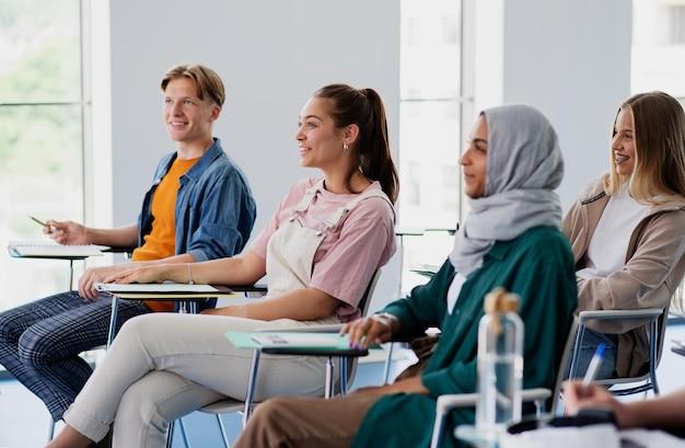 Um grupo de estudantes universitários multiétnicos sentados em uma sala de aula dentro de casa, estudando.