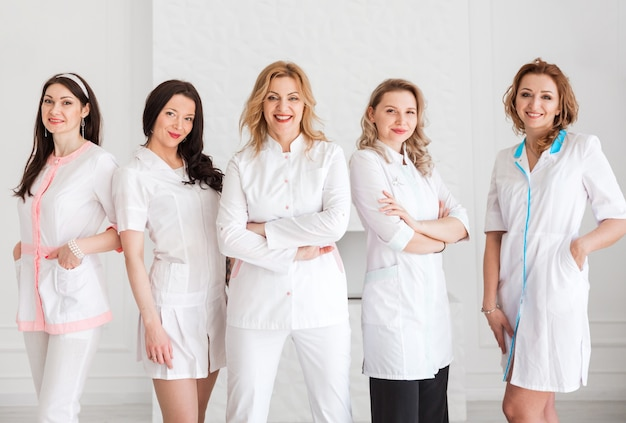 Um grupo de felizes lindas médicas, enfermeiras, estagiários, assistentes de laboratório em uniforme branco posando no contexto de uma parede branca.