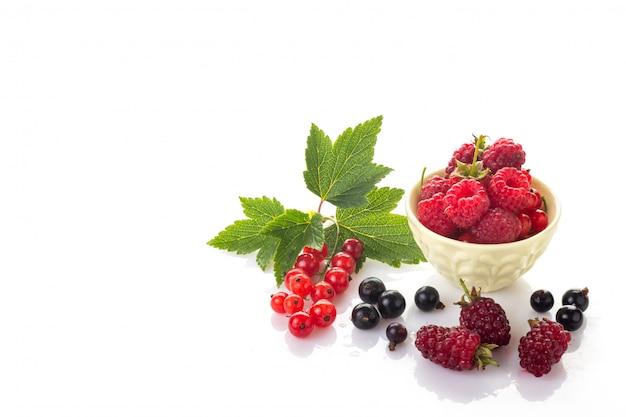 Um grupo de frutas frescas. groselha vermelha e preta com folhas verdes, framboesas em uma tigela e loganberry isolado