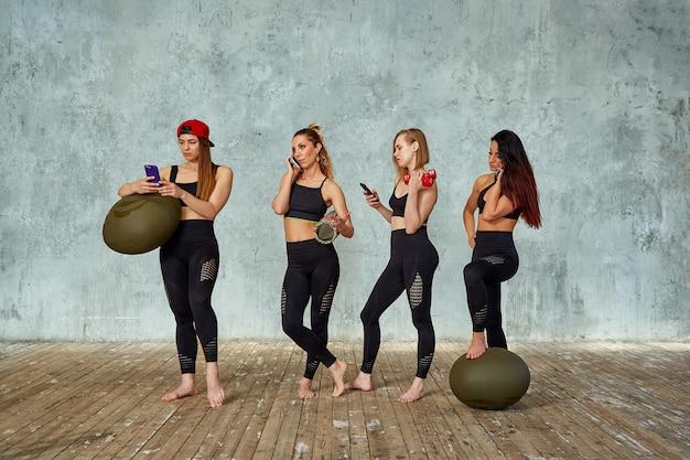 Um grupo de garotas bonitas fitness em uma sala de fitness perto de uma parede cinza com adereços para treinamento, emocionalmente falando ao telefone. copie o espaço, plano de fundo cinza.