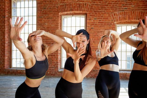 Um grupo de garotas bonitas, mãos escondendo o rosto.