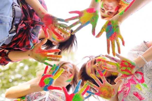 Um grupo de garotas jovens mostra as palmas das mãos sujas com tintas coloridas