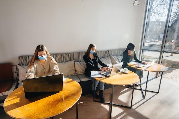 Um grupo de garotas mascaradas mantém distância social em um café enquanto trabalha com laptops