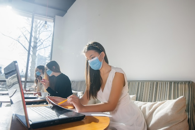 Um grupo de garotas mascaradas mantém uma distância social em um café enquanto trabalha com laptops.