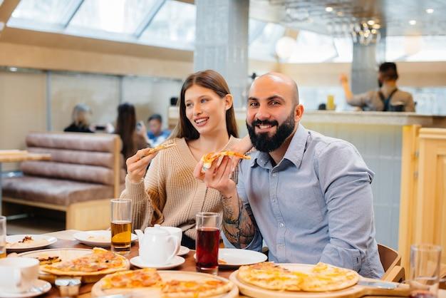 Um grupo de jovens amigos alegres está sentado em um café conversando e comendo pizza. almoço na pizzaria. Foto Premium