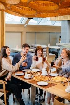 Um grupo de jovens amigos alegres está sentado em um café conversando e comendo pizza. almoço na pizzaria.