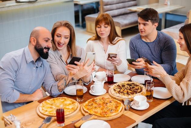 Um grupo de jovens amigos alegres está sentado em um café, conversando e tirando selfies ao telefone. almoço na pizzaria.