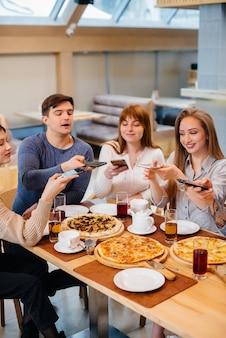 Um grupo de jovens amigos alegres está sentado em um café conversando e tirando selfies ao telefone