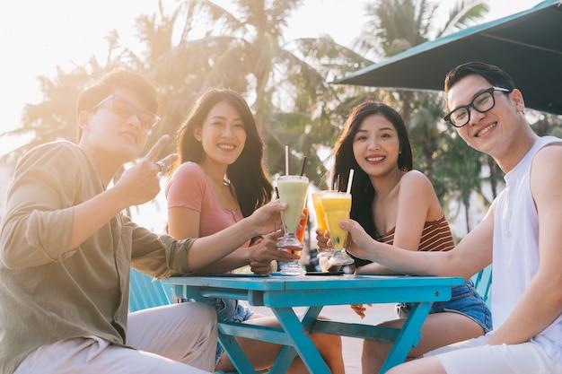 Um grupo de jovens asiáticos aproveita uma viagem ao mar nas férias de verão