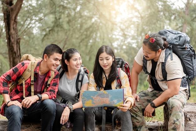 Um grupo de jovens asiáticos está planejando e olhando mapas para acampar na floresta.